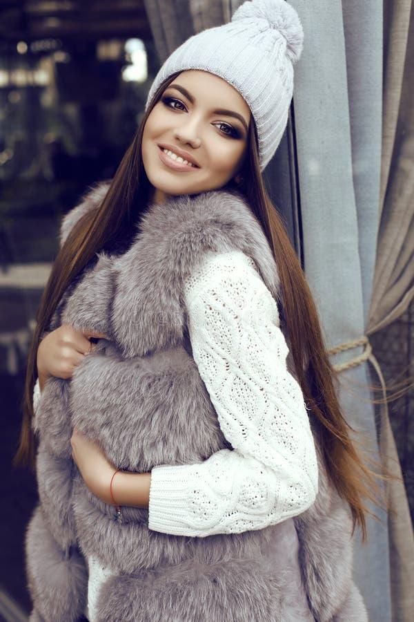 La muchacha del encanto con el pelo recto oscuro lleva el abrigo de pieles lujoso y el sombrero hecho punto fotografía de archivo libre de regalías