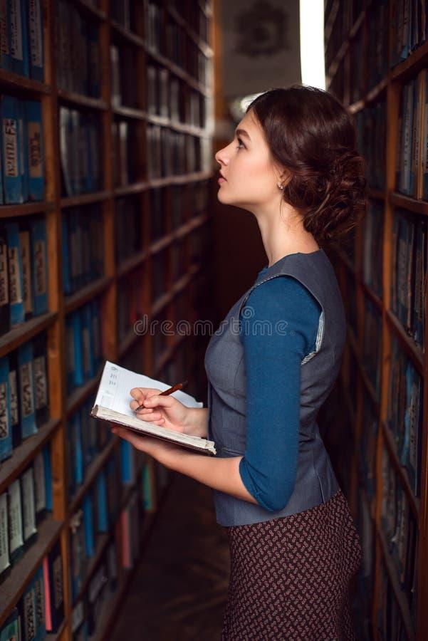 La muchacha del estudiante hace notas en el cuaderno fotografía de archivo