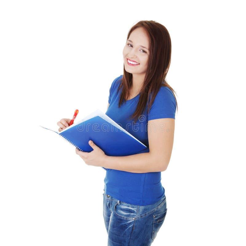 La muchacha del estudiante se está colocando con la pluma y el cuaderno. fotos de archivo