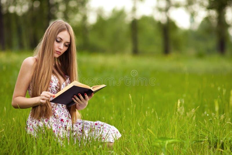 La muchacha del estudiante se sienta en césped y lee el libro de textos. imagen de archivo libre de regalías
