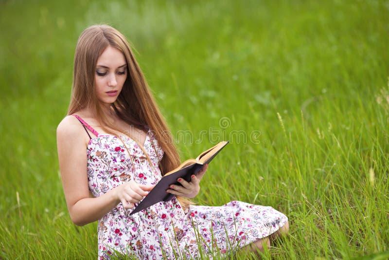 La muchacha del estudiante se sienta en césped y lee el libro de textos. fotografía de archivo libre de regalías