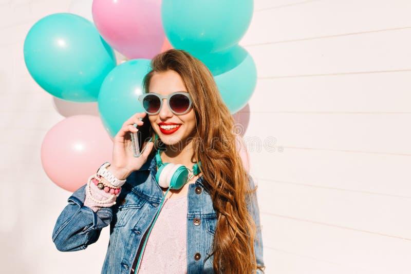 La muchacha del feliz cumpleaños con una sonrisa de hollywood acepta enhorabuena por el manojo de la tenencia del smartphone de g fotografía de archivo libre de regalías