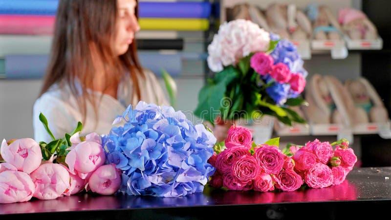 La muchacha del florista hace un ramo en un salón de la flor, primer fotos de archivo libres de regalías