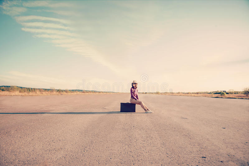 La muchacha del inconformista se sienta en la maleta fotografía de archivo