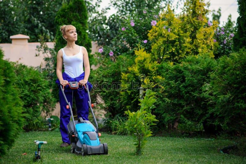 La muchacha del jardinero está cortando la hierba con el cortacéspedes imagenes de archivo