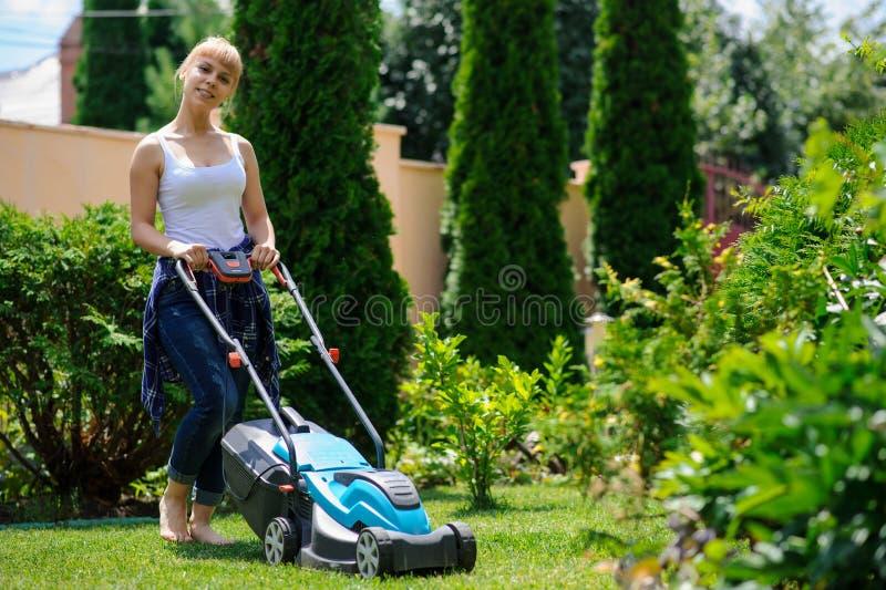La muchacha del jardinero está cortando la hierba con el cortacéspedes imagen de archivo libre de regalías