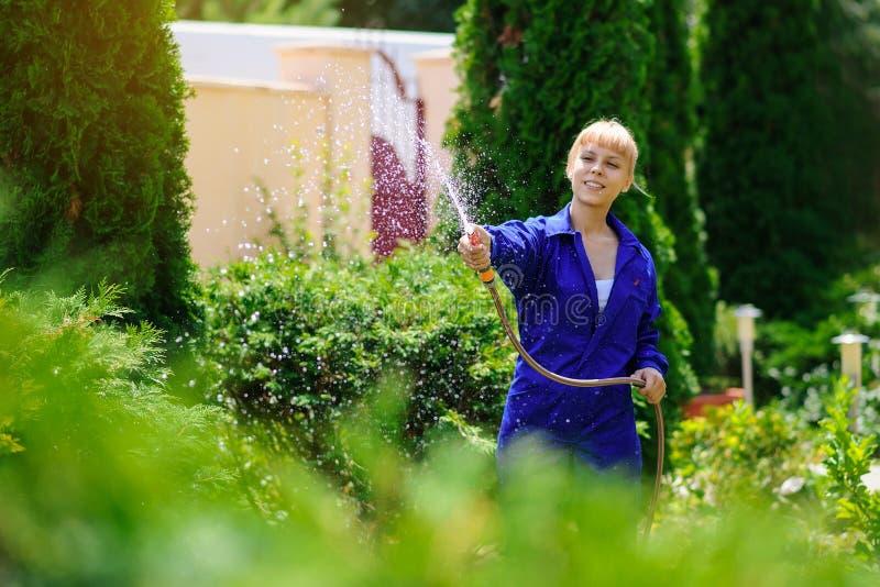 La muchacha del jardinero está regando el jardín imagen de archivo libre de regalías