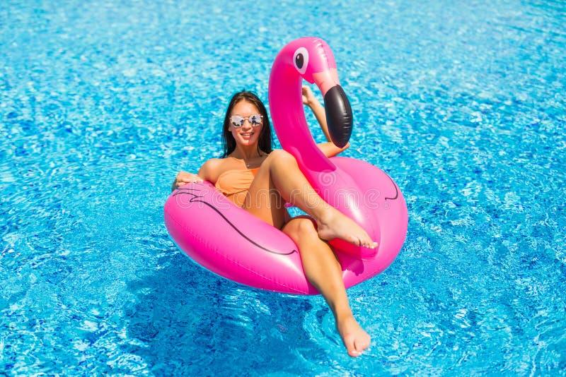 La muchacha del moreno se sienta en flamencos inflables del colchón y se relaja en la piscina Partido de piscina fotos de archivo