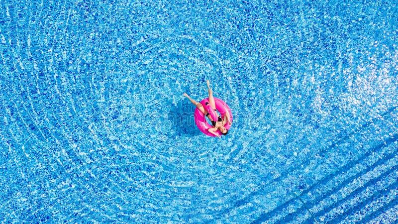 La muchacha del moreno se sienta en flamencos inflables del colchón en la piscina desde arriba imagenes de archivo