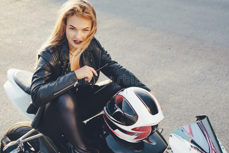 La muchacha del motorista en un cuero viste en una motocicleta imagen de archivo