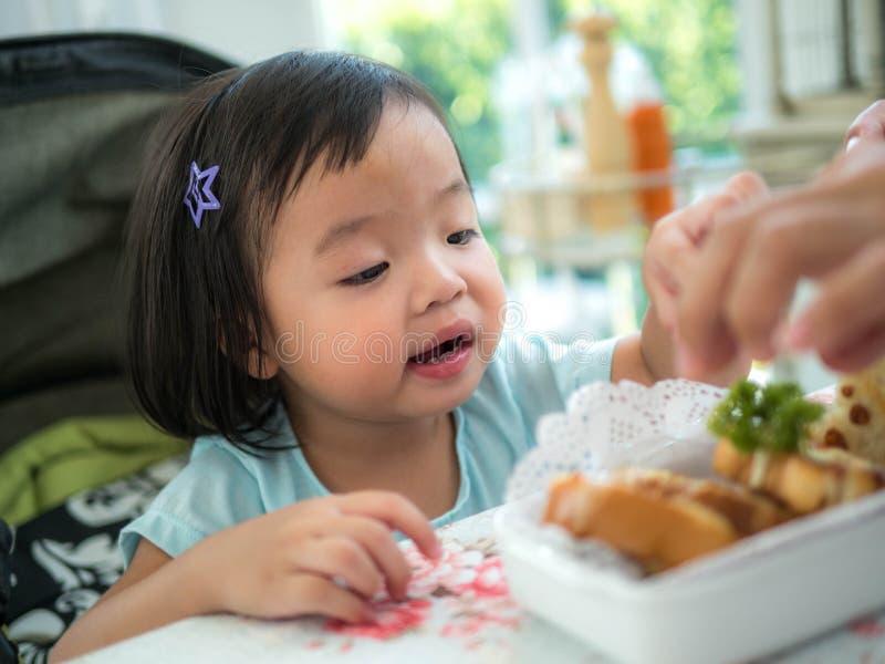 La muchacha del niño come el pan La muchacha feliz del niño tiene un pan del bocado en la cocina foto de archivo