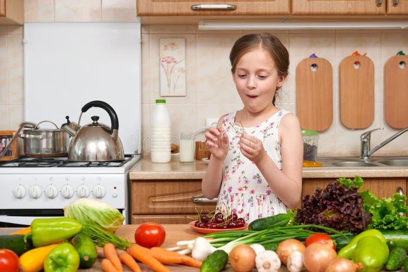 La muchacha del niño come las cerezas, frutas y verduras en la cocina casera interior, concepto sano de la comida imagen de archivo