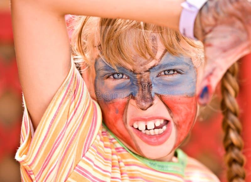 La muchacha del niño con la pintura en cara en cabritos aporrea. foto de archivo