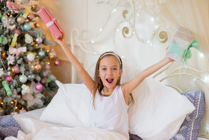 La muchacha del niño despierta en su cama por mañana de la Navidad fotos de archivo libres de regalías