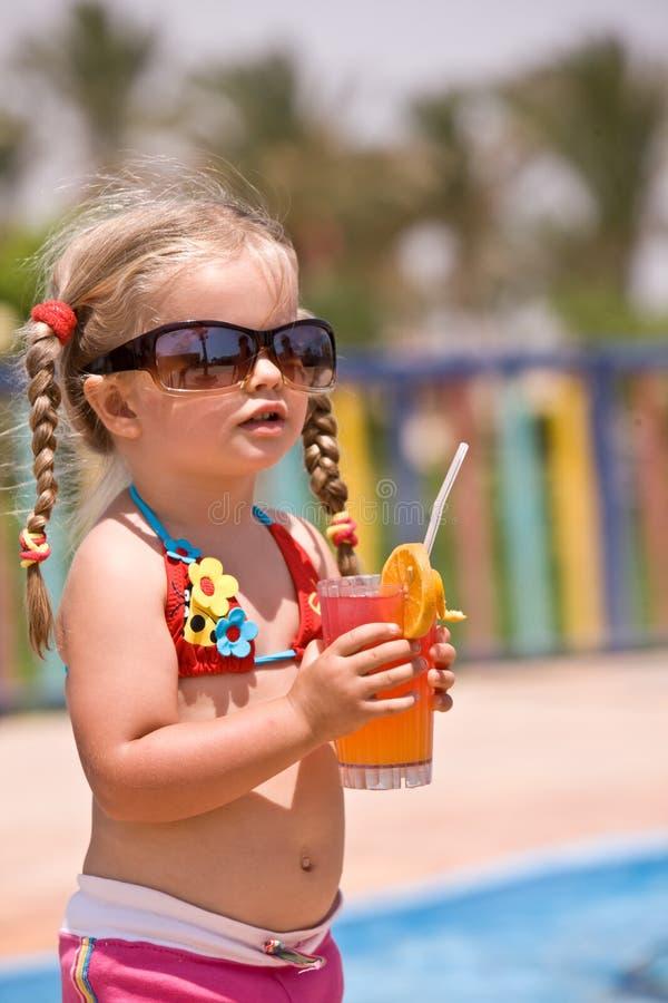 La muchacha del niño en gafas de sol bebe el zumo de naranja. imagenes de archivo