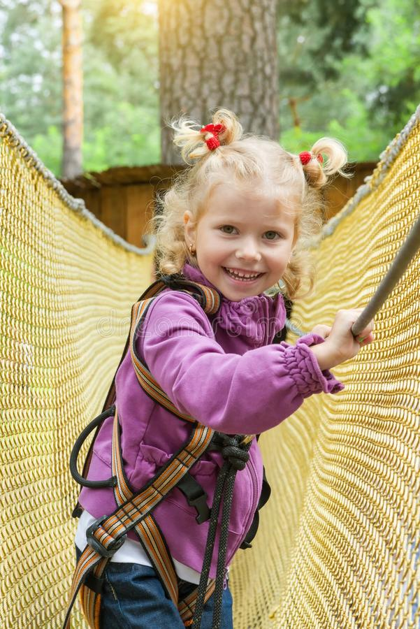 La muchacha del niño es 4 años en parque del cable de alta tensión de la aventura que sube, forma de vida activa de niños imagen de archivo libre de regalías
