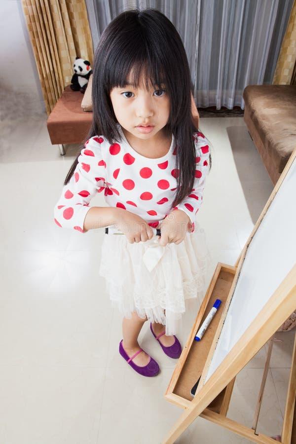 La muchacha del niño escribe en un tablero blanco con la pluma de la marca negra fotos de archivo