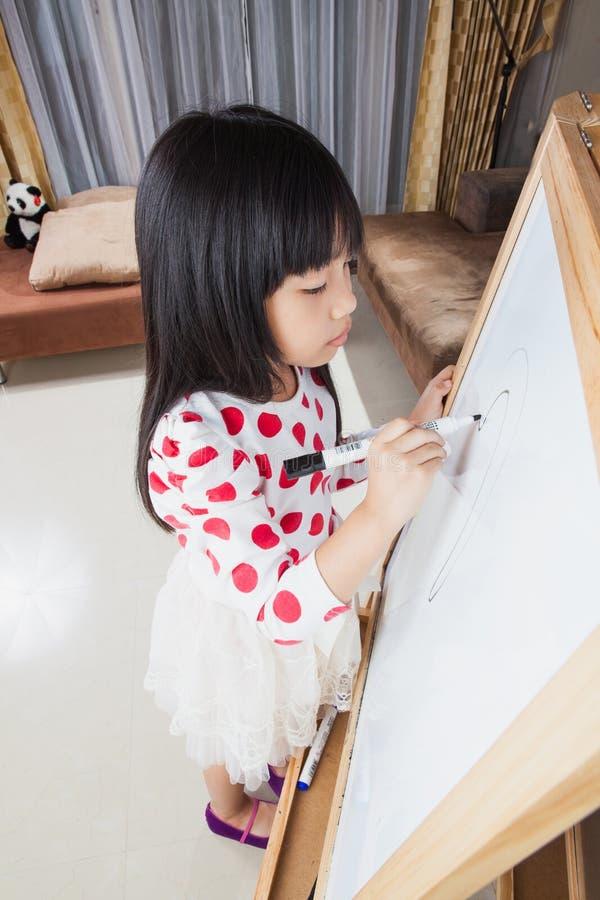 La muchacha del niño escribe en un tablero blanco con la pluma de la marca negra fotografía de archivo libre de regalías