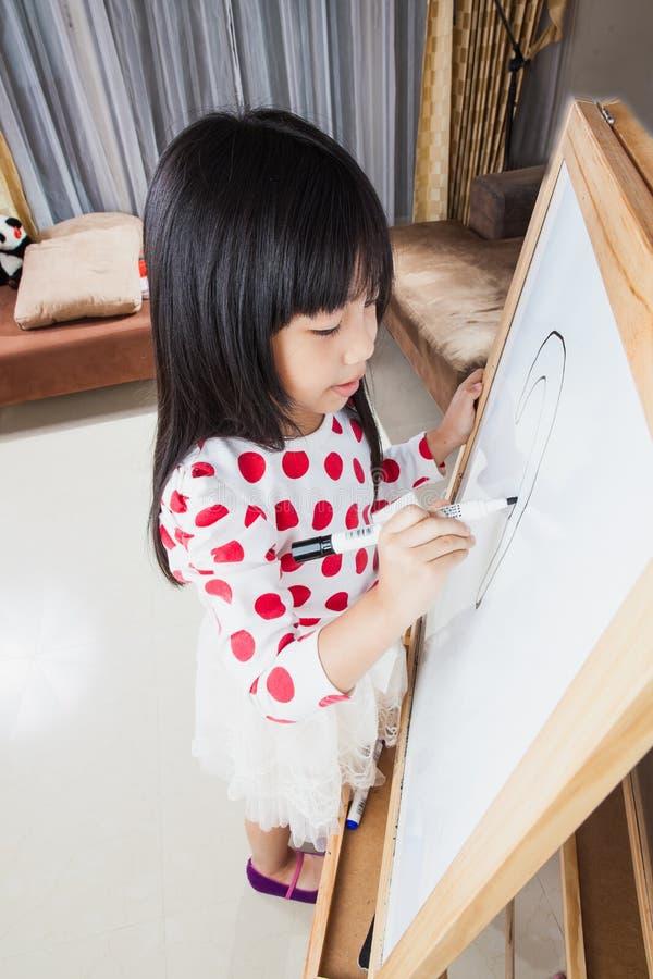 La muchacha del niño escribe en un tablero blanco con la pluma de la marca negra imágenes de archivo libres de regalías