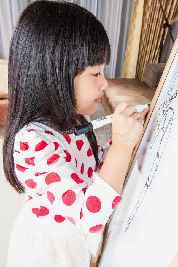 La muchacha del niño escribe en un tablero blanco con la pluma de la marca negra imagen de archivo