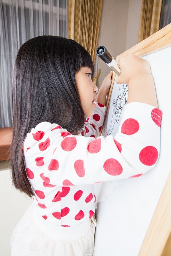 La muchacha del niño escribe en un tablero blanco con la pluma de la marca negra imagen de archivo libre de regalías