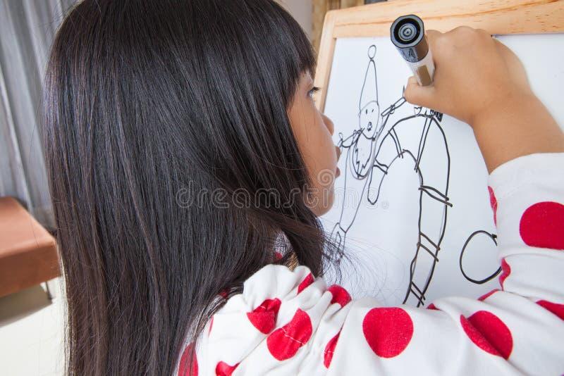La muchacha del niño escribe en un tablero blanco con la pluma de la marca negra fotos de archivo libres de regalías