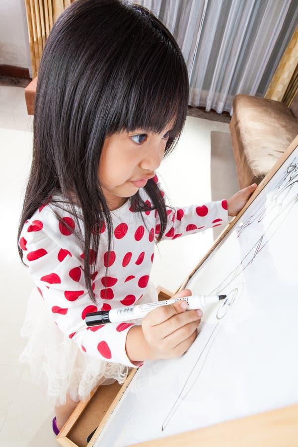 La muchacha del niño escribe en un tablero blanco con la pluma de la marca negra foto de archivo libre de regalías