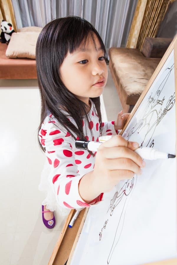 La muchacha del niño escribe en un tablero blanco con la pluma de la marca negra fotografía de archivo