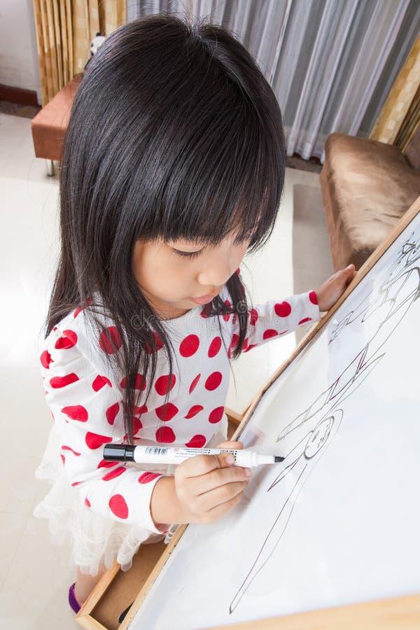 La muchacha del niño escribe en un tablero blanco con la pluma de la marca negra imagenes de archivo