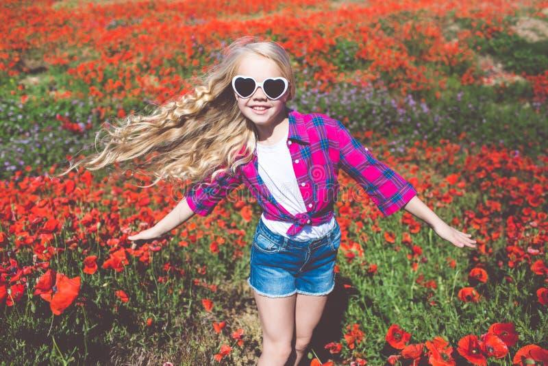 La muchacha del niño está llevando las gafas de sol y la ropa casual de la moda en primavera coloca con el ramo de amapolas fotos de archivo libres de regalías