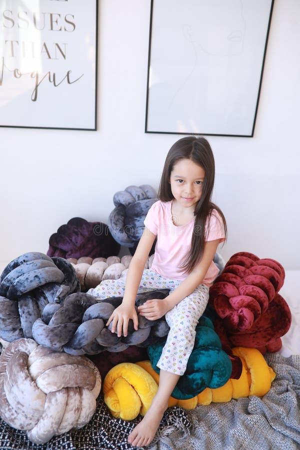 La muchacha del niño juega entre las almohadas inusuales en pijamas foto de archivo libre de regalías
