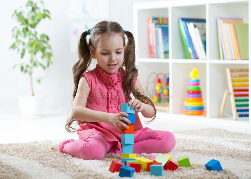 La muchacha del niño que juega con el bloque juega en centro de guardería fotografía de archivo libre de regalías