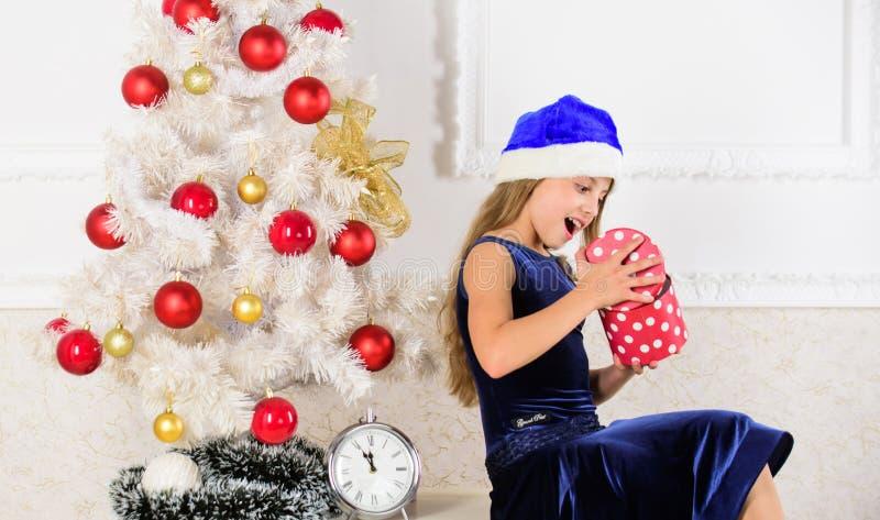 La muchacha del niño se sienta cerca de la caja de regalo del control del árbol de navidad Sombrero de santa de la niña emocionad imágenes de archivo libres de regalías