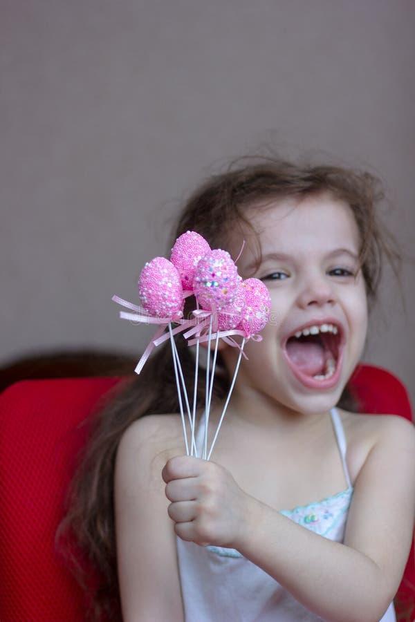 La muchacha del niño sostiene los huevos de Pascua rosados en manos y risa o sonrisa fotos de archivo libres de regalías
