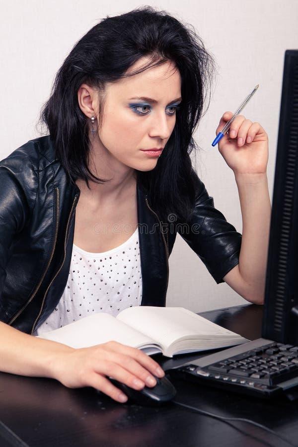 La muchacha del oficinista que trabaja en un ordenador y hace los expedientes en un diario en un fondo blanco foto de archivo