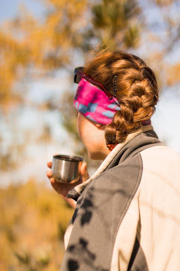 La muchacha del pelirrojo bebe té de un termo en otoño en la montaña fotografía de archivo libre de regalías