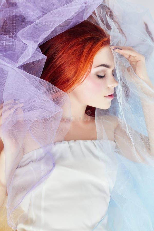 La muchacha del pelirrojo sueña, maquillaje brillante, piel limpia, cuidado facial La muchacha del pelirrojo en un vestido colore foto de archivo