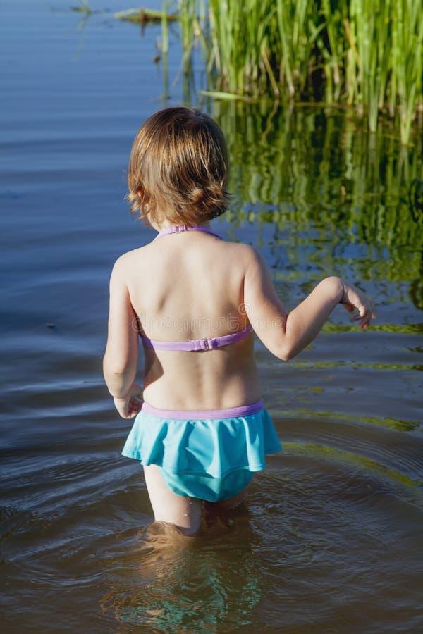 La muchacha del pequeño niño entra el agua del lago nadar holida foto de archivo libre de regalías
