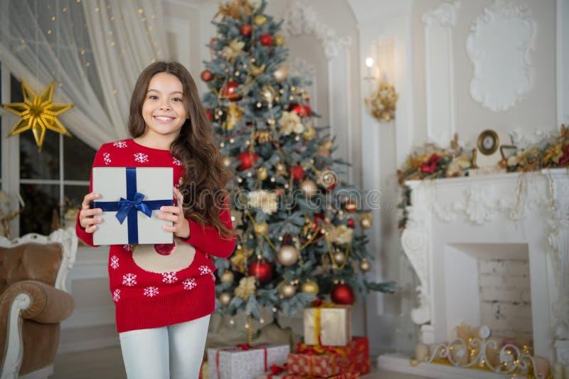 La muchacha del pequeño niño le gusta el presente de Navidad Feliz Año Nuevo pequeña muchacha feliz en la Navidad Navidad Es uste imagen de archivo