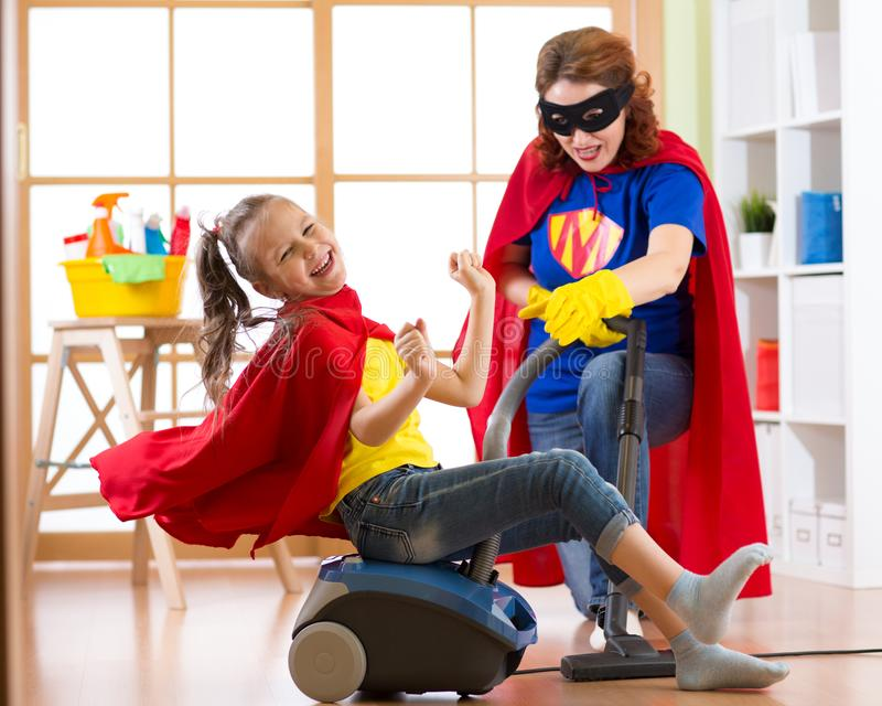 La muchacha del pequeño niño y su madre juegan mientras que hace limpieza en casa fotos de archivo libres de regalías