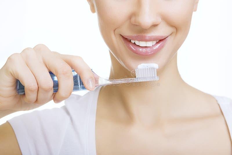 La muchacha del primer con los dientes de la limpieza del cepillo de dientes en casa, blanquea toque de bocina foto de archivo