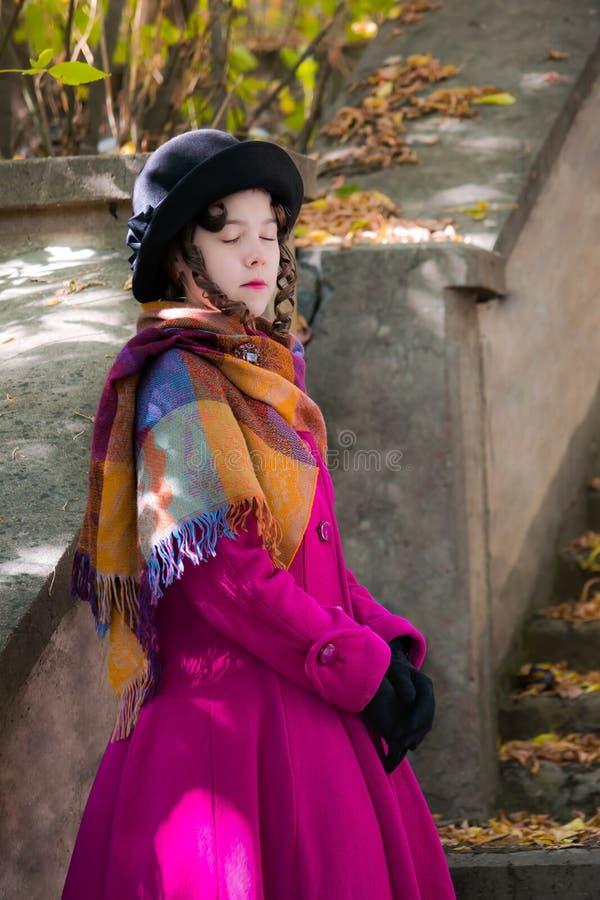 La muchacha del retrato en una capa carmesí brillante con los ojos se cerró fotografía de archivo