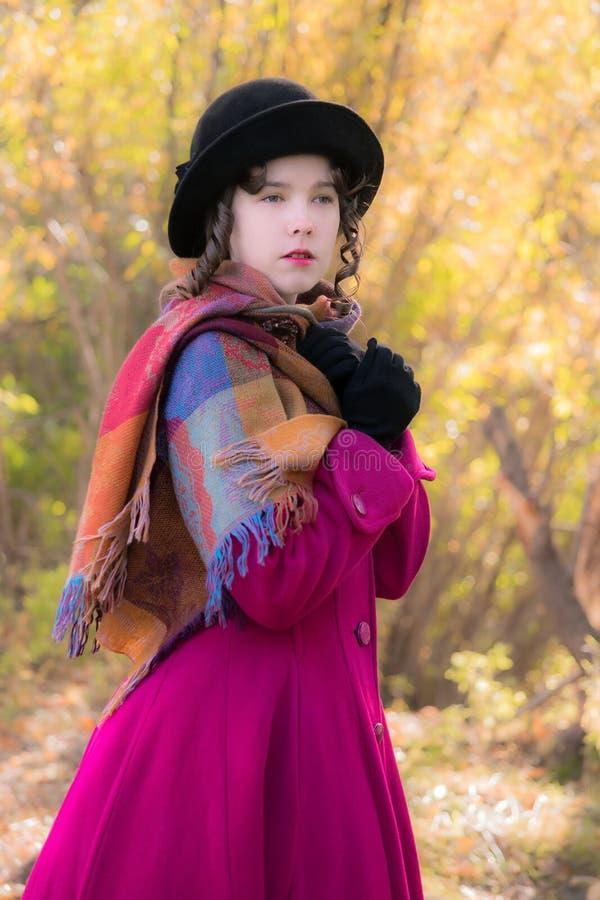 La muchacha del retrato en una capa carmesí brillante congela en el viento imagenes de archivo