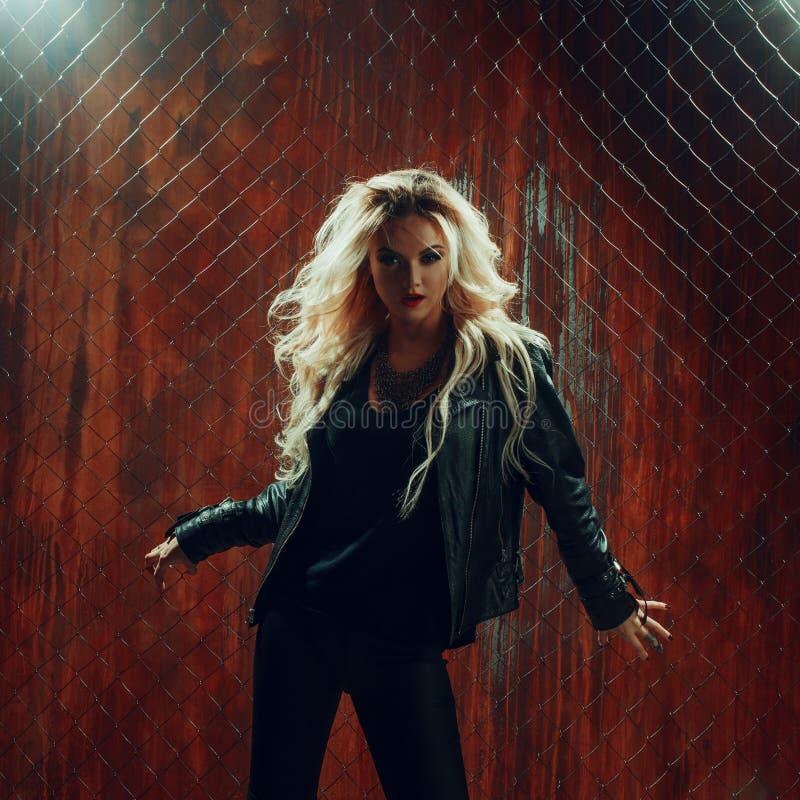 La muchacha del rollo del ` del ` n de la roca, mujer hermosa joven baila en callejón oscuro, contra la malla de la cerca imagen de archivo libre de regalías