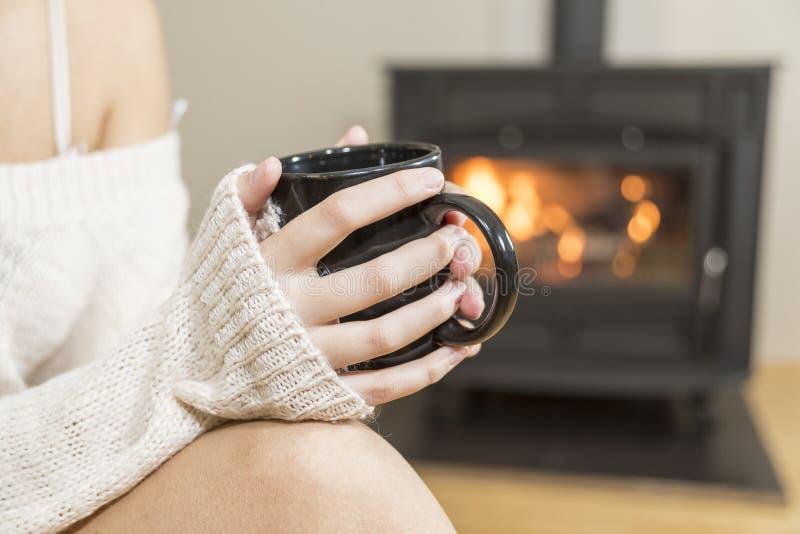 La muchacha delante de la chimenea en calcetines del invierno imágenes de archivo libres de regalías