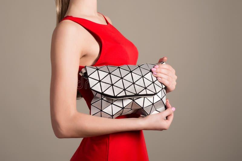 La muchacha delgada atractiva en un vestido de noche del rojo sostiene un bolso elegante de triángulos plateados foto de archivo libre de regalías