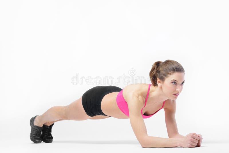 La muchacha delgada bronceada atractiva joven realiza ejercicios de los deportes fotos de archivo