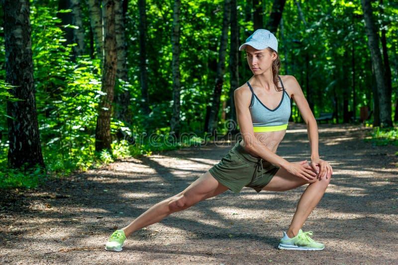 la muchacha delgada con una figura deportiva realiza ejercicios foto de archivo libre de regalías