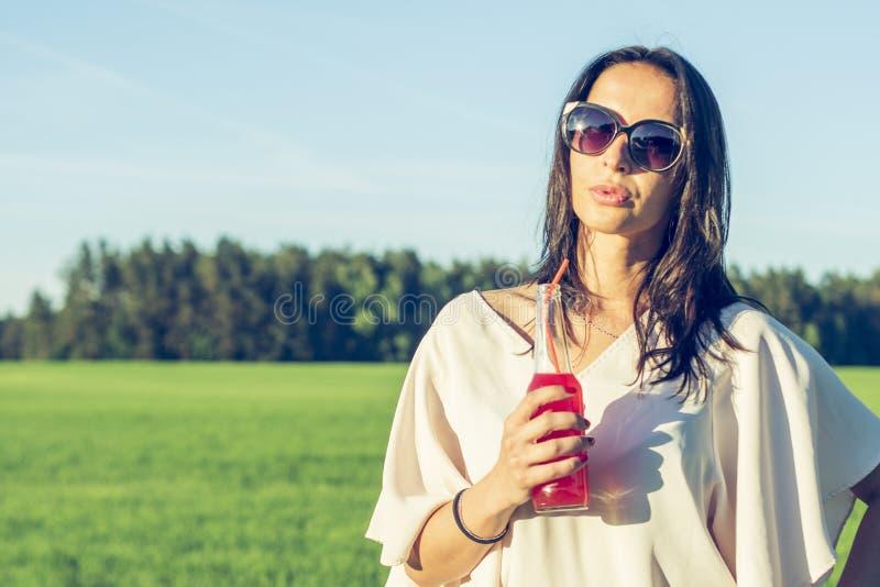 La muchacha delgada de Youn con los vidrios y el pelo rizado sonríen y beben un cóctel rojo alcohólico o sin alcohol a través de  imagen de archivo