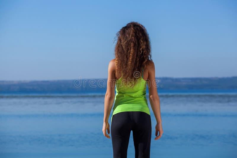 La muchacha delgada joven en el traje negro y verde claro de los deportes que se sienta después de activar camina en la playa imagenes de archivo